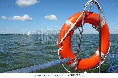 Red lifebuoy on yacht, on lake's background
