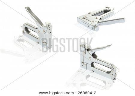 Three staple guns at white; background