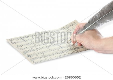 feather and music sheet at white background