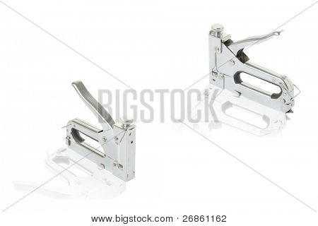 three staple guns at white; background