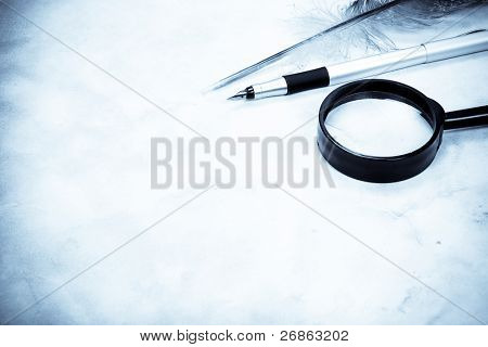 magnifying glass and feather closeup