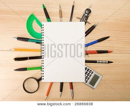 pen, pencil and magnifier under checked notebook on wood texture