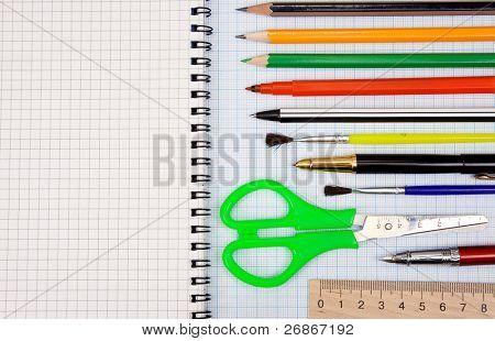 pens, pencils, paint brush and scissors on graph grid paper