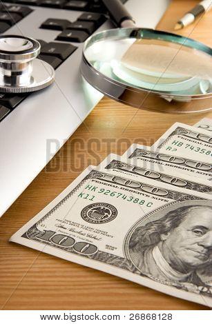 estetoscopio en teclado y dólares con lápiz en la mesa de madera