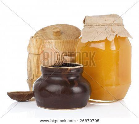 Gläser und Topf voller Honig isoliert auf weißem Hintergrund