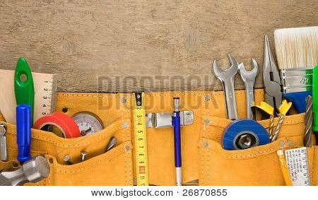 tools in belt on wooden texture