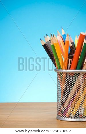pen and pens in holder on blue background