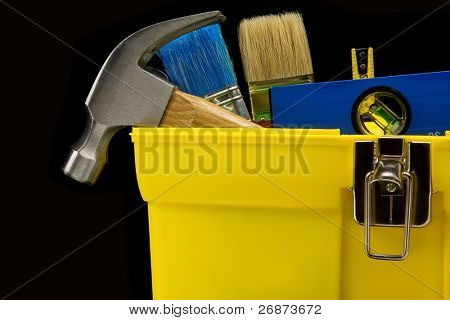 tools in construction toolbox isolated on black background