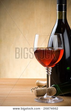 glass and bottle of wine on wood background