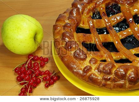 Fresh sweet pie with bilberry on a yellow plate