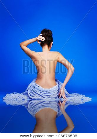 Bare beautiful young woman sitting against blue background