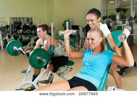 Young woman lifting a dumb-bell in the gym assisted by her personal trainer