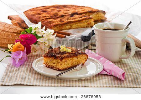 Ein Blatt-Kuchen mit Zimt-Zucker-Butter und einer heißen Tasse Kaffee