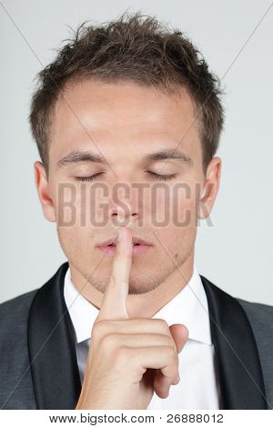 Portrait of businessman showing silence gesture with his forefinger by mouth