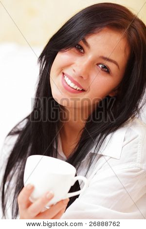 Closeup portrait of a happy young beautiful woman with a white cup