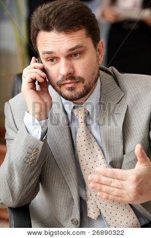 Portrait of a mature business man screaming in his cellphone in office environment