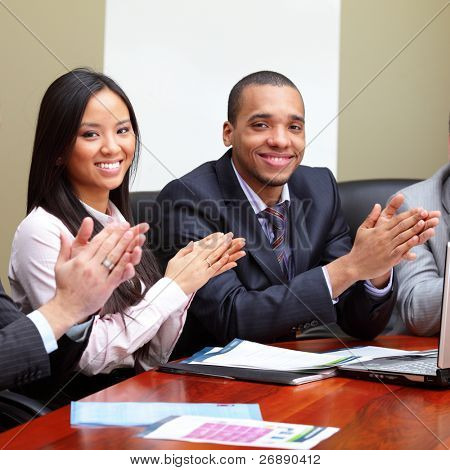 Multi ethnic business group greets you with clapping and smiling. Focus on woman