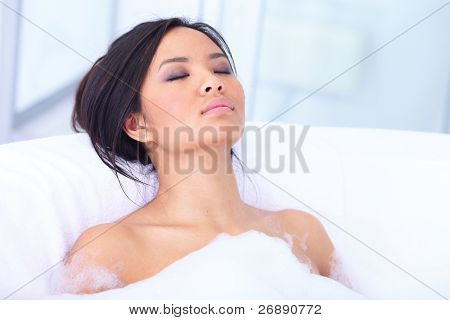 Relaxed asian woman resting in her bathtub