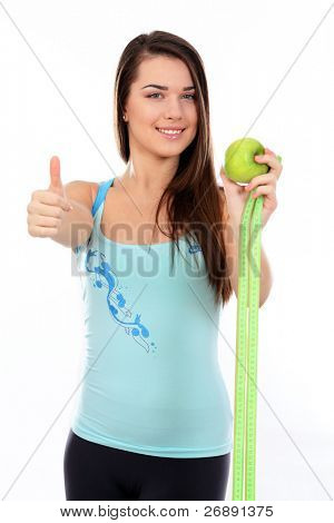 Portrait of a young sport woman holding apple and measuring tape and giving thumbs-up gesture over white background