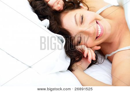 Beautiful woman lying on the bed in the morning and laughing sincerely