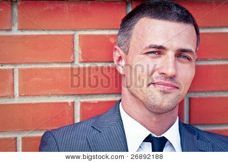 Closeup portrait of a handsome businessman against red brick wall