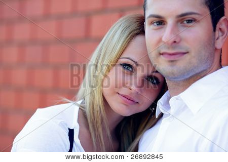 Lovely couple standing near the wall and smiling