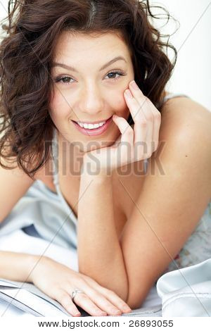 Beautiful woman lying on the sofa and smiling