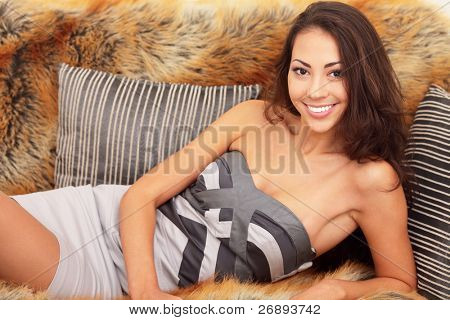 Portrait of a cheerful smiling young lady lying on the sofa with fur