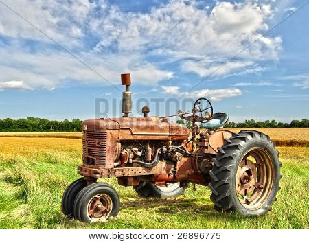 red old rusty tractor in a field