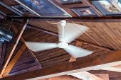 Ceiling Fan For Summer And Winter. Ceiling Fan On Vaulted Wood Ceiling In The Living Room Of Modern  poster