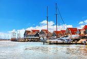 Volendam, Netherlands. High-speed motorboat by docks near old traditional town not far from Amsterda poster