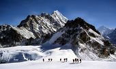 stock photo of sherpa  - this is a photo of climbers and sherpas making a glacier traverse on the way to mera peak. in the far distance you can see the everest/lhotse massive.