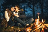 Pretty Young Couple Drinking Hot Beverage In The Forest Near Bonfire. poster
