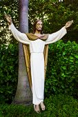 Community Catholic Church Courtyard With A Jesus Wooden Figure. Jesus Figure Is Approx. 5 Feet Tall  poster