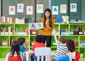 Asian Female Teacher Teaching And Asking Mixed Race Kids Hand Up To Answer In Classroom,kindergarten poster