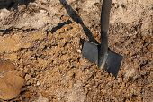 foto of land development  - Shovel putted into heap of ground - JPG