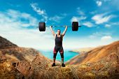 Weightlifter takes a weight on the top of mountain poster