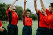Energetic female rugby players celebrating together poster