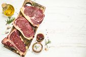 Raw Meat Beef Steak. Black Angus Prime Meat Set - Ribeye, Striploin, T-bone Steaks On Cutting Board. poster