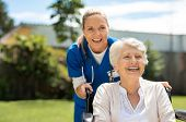 Happy nurse and elderly woman sitting in wheelchair enjoying outdoor. Beautiful nurse with laughing  poster