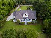 Aerial view of large home with new roof on wooded grassy property poster