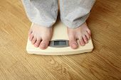Weighloss - young man on a weighing scale
