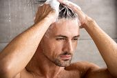 Close Up Portrait Of Adult Man Washing Hair With Shampoo And Taking Shower poster