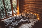 Rustic interior decoration of log cabin bedroom. Cozy warm blanket on bed by window. poster