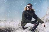 A handsome brutal man wearing a parka and sunglasses in the countryside. Fashion for men. Autumn, wi poster