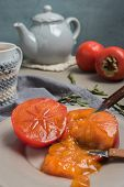 Persimmon Fruit On The Plate And Lemon Tea. Rustic Background In Vintage Style poster
