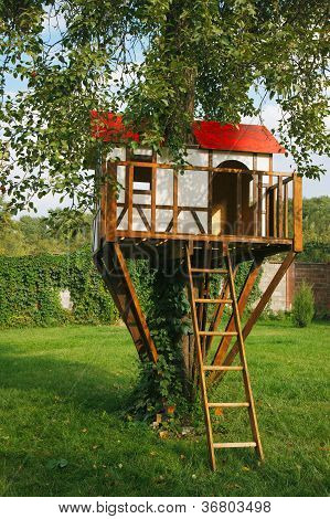 Cute small tree house for kids on backyard.