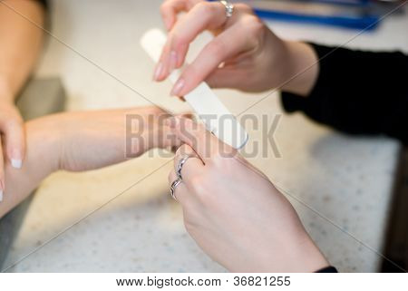 Female Hands Make Manicure By Nailfile For Woman