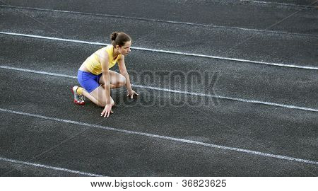 Athletic Teenage Girl In Start Position On Track .