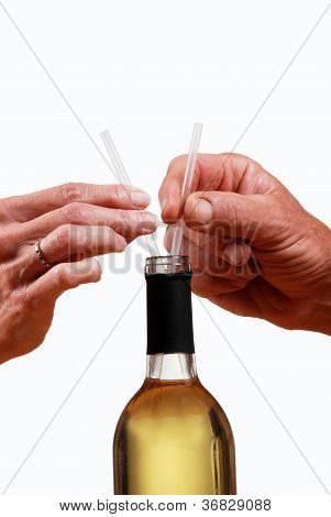 Wine Bottle With Hands Holding Two Straws.